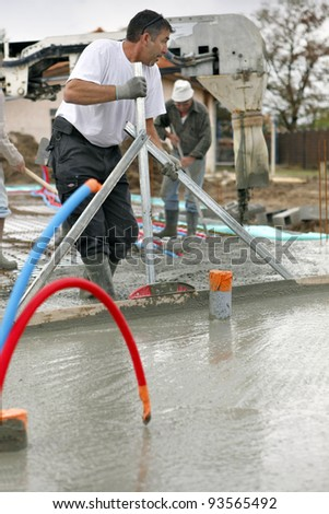 Workers pouring a cement foundation - stock photo