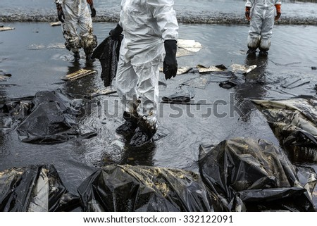 Workers remove crude oil from a beach, Crude oil on oil spill is accident  on a beach at  Ao Prao Beach, Koh Samet, Rayong, Thailand - stock photo