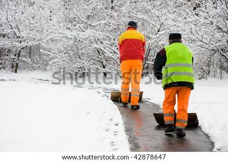 Workers removing first snow from pavement - stock photo