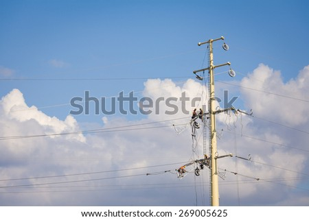 Workers repairing a high voltage industrial power energy line. Great for energy, safety and technology themes. : Almada, Portugal - September 29, 2008  - stock photo