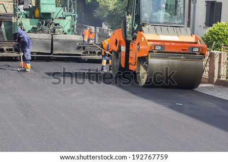 Workers, roller and operating asphalt paver machine during road construction and repairing works  - stock photo