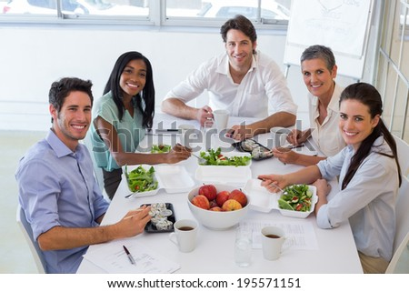 Workers smile at camera while eating healthy lunch in the office - stock photo