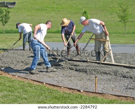 Workers smooth a concrete slab - stock photo