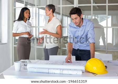 Workers talking and looking over plans in the office - stock photo