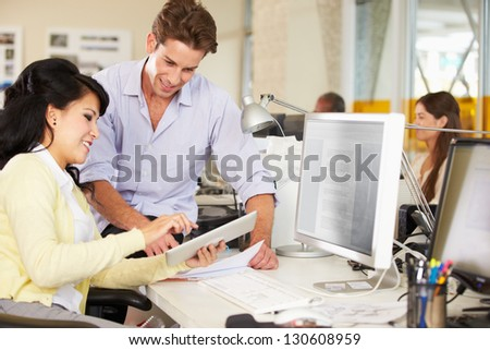 Workers Using Digital Tablet In Busy Creative Office - stock photo