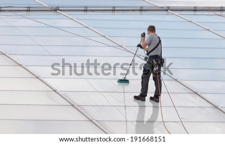 Workers washing the roof made of glass of a modern office building - stock photo