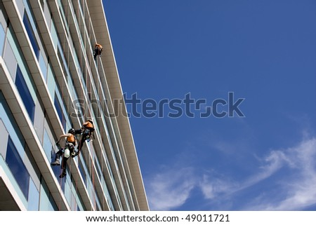 Workers washing the windows facade of a modern office building (cleaning glass service) - stock photo