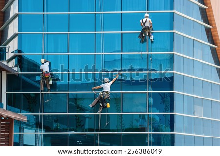 workers washing windows of the modern skyscraper building - stock photo