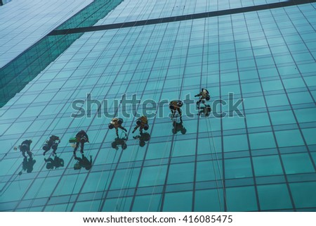 workers washing windows of the modern skyscraper building. Men cleaning high tower on Moscow city