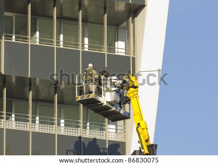 Workers wearing a safety harness on a Cherry Picker - stock photo