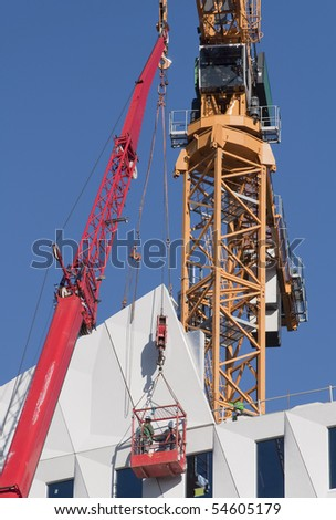 Workers wearing safety harness in a hoist basket - stock photo