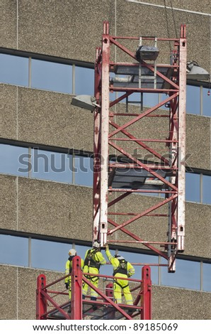 Workers wearing safety harness reaching for lifted element of a tower crane - stock photo