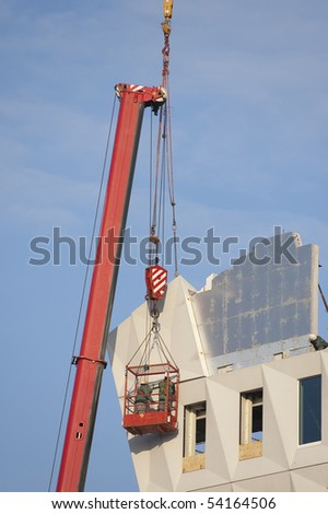 Workers wearing safety harnesses are assisting the placing of a prefab concrete element - stock photo