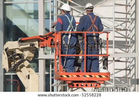 Workers wearing safety harnesses on an aerial access platform - stock photo