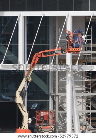 Workers wearing safety harnesses on an aerial access platform at a construction site - stock photo
