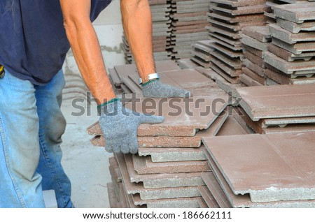 Workers were moving a lot of brown roof shingles to the roof to make a step towards the roof. - stock photo