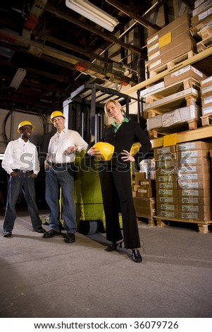 Workers with female boss in storage warehouse - stock photo