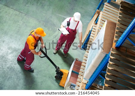 workers with fork pallet truck stacker in warehouse loading furniture panels - stock photo