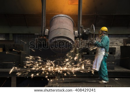 Workers with helmet inside a foundry - stock photo
