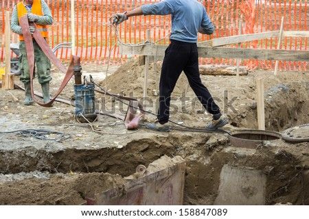 workers with Industrial Submersible Water Pump cleaning rainwater drainage - stock photo
