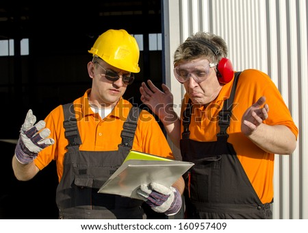 workers with paper folder in front of industrial hall