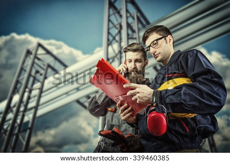workers with protective helmet in front of industrial refinery oil pipes - stock photo