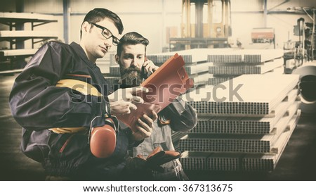 workers with protective uniforms in front of metal proflies - toned image, retro film filtered in instagram style