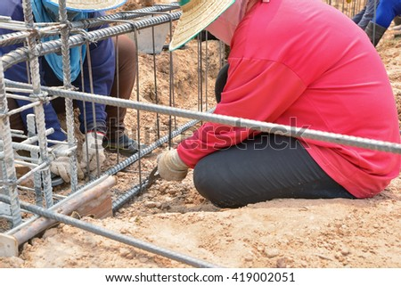 Workers women using steel wire at construction site