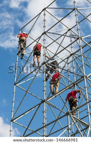 Workers working on scaffolding against a blue sky - stock photo