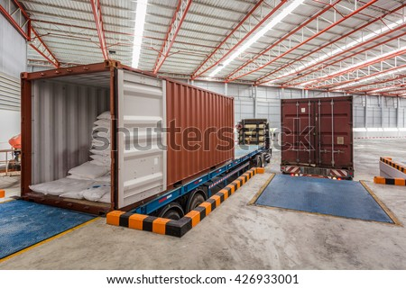 Workers working on trucks at loading meal at dock shipping industry in warehouse  - stock photo