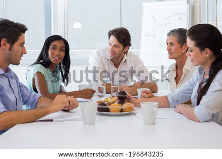 Workers working while enjoying hot drinks and muffins in the office - stock photo