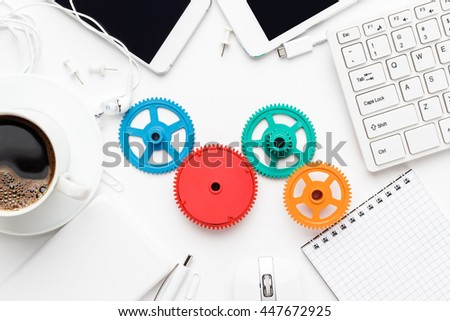 workflow and teamwork concepts with colorful gears different gadgets and office stationery on the white office table - stock photo