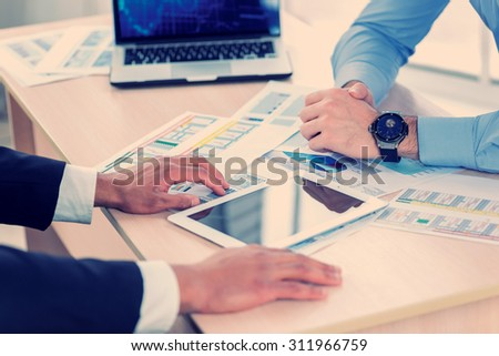 Workflow in the office. Close-up view of the hands and the plate on the table while two successful businessman sitting at the table against each in the business in formal wear and work at a laptop. - stock photo
