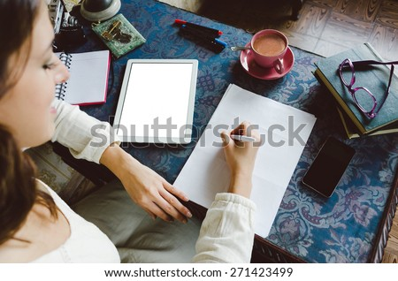 Working at home concept. Entrepreneur business woman writing and taking notes using her digital tablet on retro desk full of objects. - stock photo