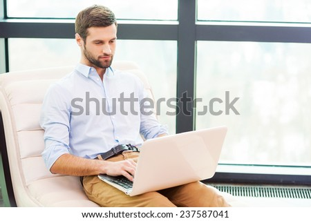 Working at home. Handsome young man working on laptop while sitting at the chair at home - stock photo