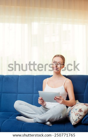 Working at pajamas. Attractive young caucasian woman holding digital tablet while sitting on the sofa at home looking at camera.  - stock photo