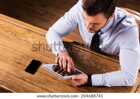 Working at the bar counter. Top view of confident young man in shirt and tie working on digital tablet while sitting at the bar counter - stock photo