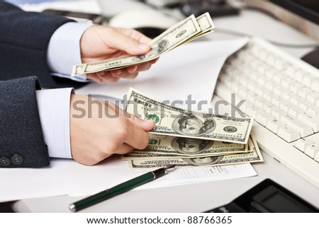 Working business man hand counting or calculating dollar currency at office workplace - stock photo