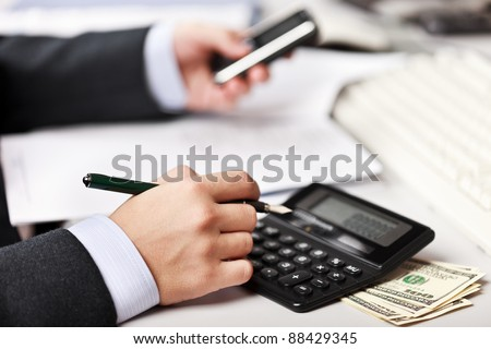 Working business man hand pen writing paper document at office workplace - stock photo