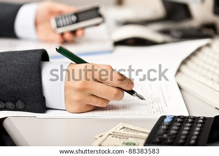 Working business man hand pen writing paper document at office workplace desk - stock photo