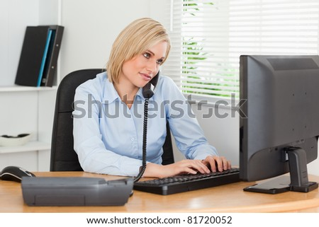 Working businesswoman in her office on the phone while typing - stock photo