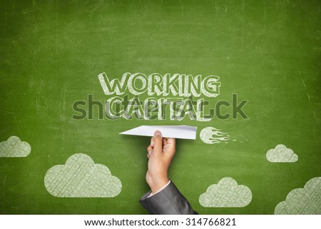 Working capital concept on green blackboard with businessman hand holding paper plane - stock photo