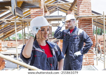working couple - woman and man - two Young adult builders on a background of iron metal beam roof trusses and summer city town with green trees at street , blue sky with clouds on backdrop - stock photo