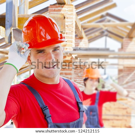 working couple - woman and man - two Young builders on a background of metal roof trusses