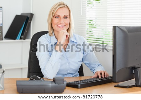 Working cute woman in front of a screen looking into camera in an office