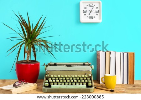 Working desk- typewriter, books and clock on the wall  - stock photo