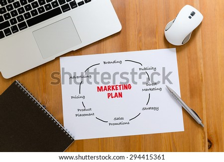 Working desk with laptop computer and paper draft showing marketing planning - stock photo