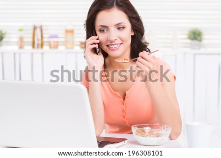 Working during breakfast. Attractive young woman having a healthy breakfast and working on laptop while sitting at the kitchen table - stock photo