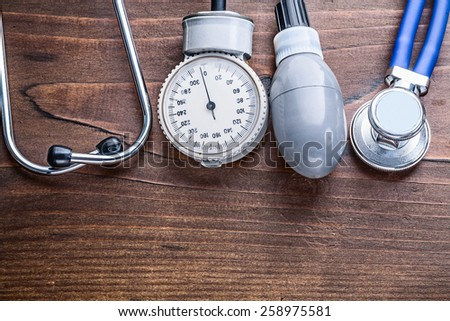 working elements of blood pressure monitor and stethoscope  on vintage wooden board horizontal version medical comcept  - stock photo