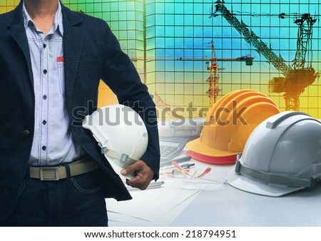 working engineering man  with white safety helmet against building and crane construction site